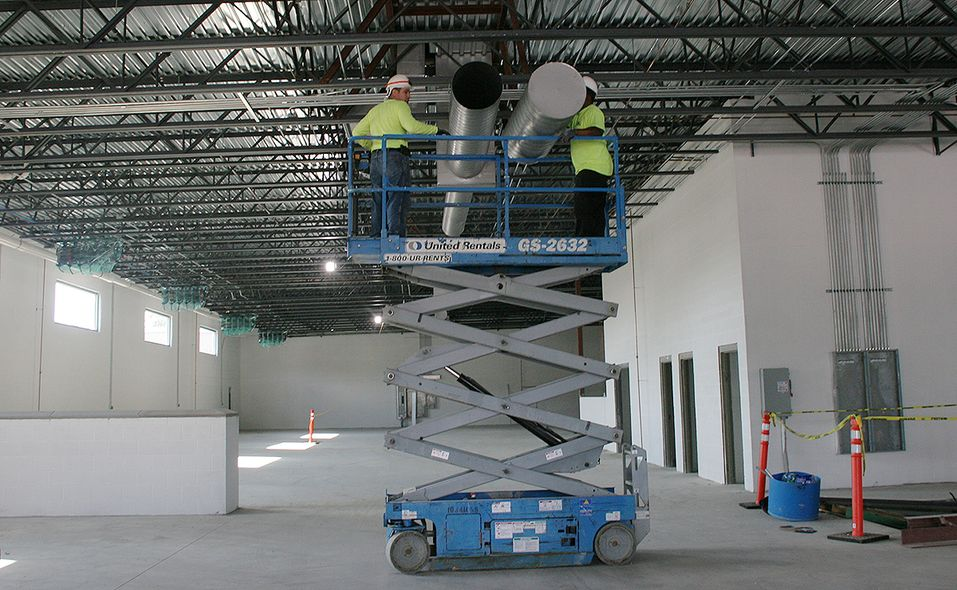 Work crews install some ducting in the lower level of the new Hennessy Ford Lincoln Atlanta dealership being built. The 88,000-square-foot, two-story main dealership building features separate Ford and Lincoln showrooms and a 48-bay service department.