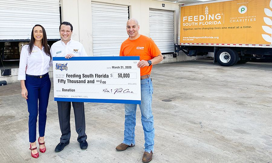 Raquel and Ryan Case of the Rick Case Automotive Group present a $50,000 donation to Paco Velez, president and CEO of Feeding South Florida, to support the organization's coronavirus relief efforts.