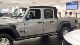 Salesman Lou Avitabile, left, talks with other staff near a new Jeep Gladiator parked inside the Flemington Chrysler-Jeep-Dodge-Ram store late in the afternoon on July 31. The store still needs to sell 16 vehicles to hit a monthly stair-step target from Fiat Chrysler.