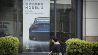 A man walks by a Tesla Model 3 sign in China