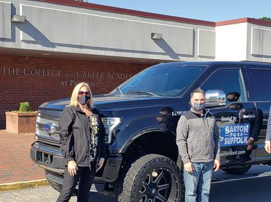 Barton Ford Service Manager Tracey Everitt, left, and Owner Bob Barton, right, donate an F-150 to the College and Career Academy at Pruden, represented by auto tech teacher Justin Nemeth.