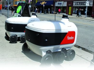 Two Yandex Rovers await their next delivery mission outside Amer's Deli in Ann Arbor, Mich. The Russian tech company aims to add to its roster of local food delivery offerings by fall.