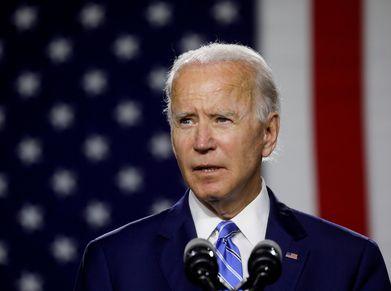President Joe Biden speaking in front of American flag