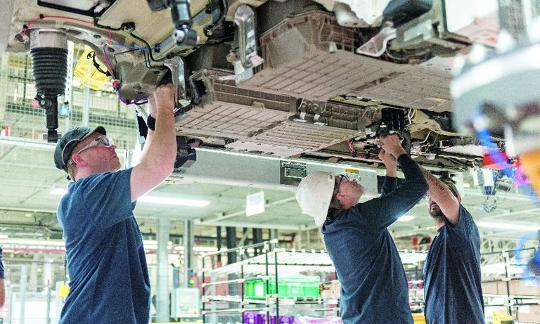 Workers at BMW's plant in Greer, S.C., install a battery on a plug-in hybrid X5 crossover.