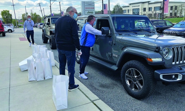 David Kelleher, by the Jeep, passes out meals to employees of his David Dodge-Chrysler-Jeep-Ram dealership in Glen Mills, Pa., which halted most operations during the pandemic.