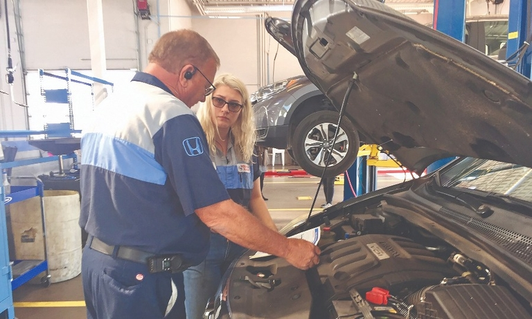 Craig Tyre, shop foreman, talks with Hannah Godbey, Express Service team leader, at Jenkins & Wynne Honda in Clarksville, Tenn.