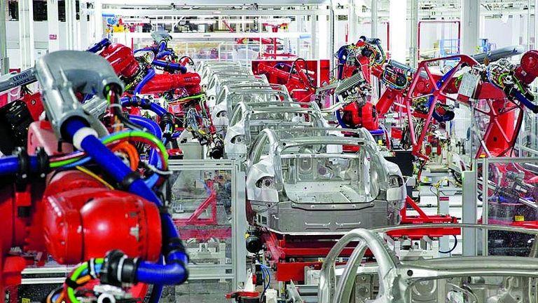 Mass-produced EVs at Tesla's Fremont, Calif., plant; left: battery-making at LG Chem