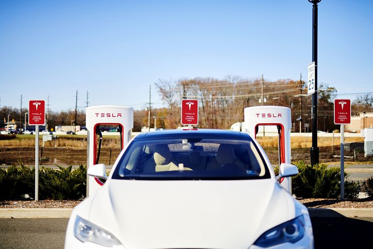 A Tesla car powers up at a charging station