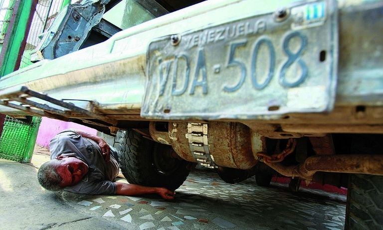 """Alfredo Gonzalez, above, and Moises Vilchez, below, hooked up their cars with cooking gas canisters. """"We're working like smugglers,"""" Gonzalez said."""