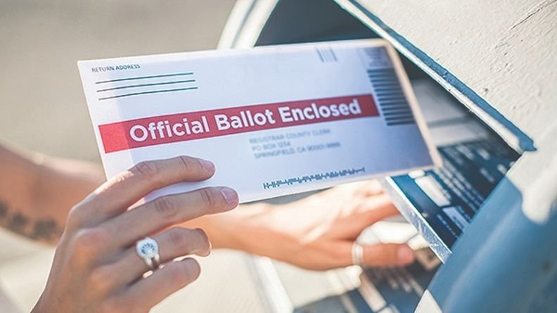 A young woman places her absentee voter ballot for the 2020 presidential election into a blue United States Postal mailbox.