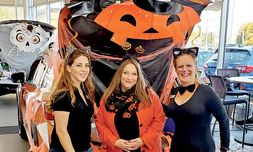 For two weeks in October, the dealership decorated showroom vehicles and welcomed customers and family members to partake in trunk-or-treat. Left to right are Linda Tavares, lead receptionist, and Michelle Clasby and Christine Clougherty, both from Internet sales.
