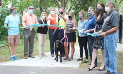 Dealer Dave Wright cuts the ribbon at the grand opening of the Dave Wright Family Dog Park.