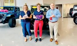 From left, Social Media Director Cassidy Dirickson, Finance Manager Kelsey Goad and General Manager Kris Childs record a Facebook video about socially distanced Halloween activities at the dealership.