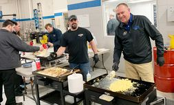 Marc VanWormer, left, paint technician, and Jeff Fries, body shop manager, cook for an employee breakfast.