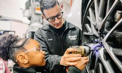 Service technician Omar Licout demonstrates righty tighty, lefty loosey for one of the dealership's scholars at Governor's Village STEM Academy.