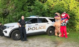 """Ira Jack Chevrolet-Cadillac showed """"Jurassic Park"""" at a free drive-in for health care workers. Police, a T. rex and track mascot Speedy were on hand."""
