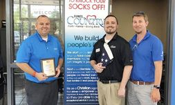 From left, Regional General Manager Jason Buxman, Internet Manager Brad Bunch and Sales Professional Jason Deters receive an award from the National Exchange Club for flying the American flag every day.