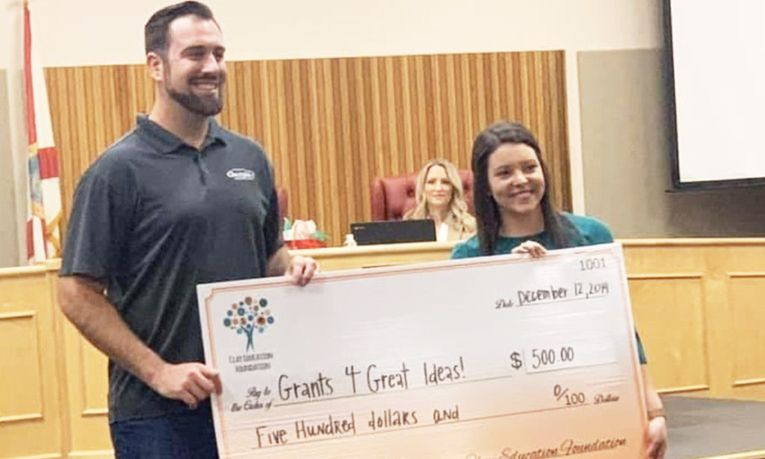 "New Car Sales Manager Zach Swarthout presents a ""Grants 4 Great Ideas"" check to the Clay Education Foundation."
