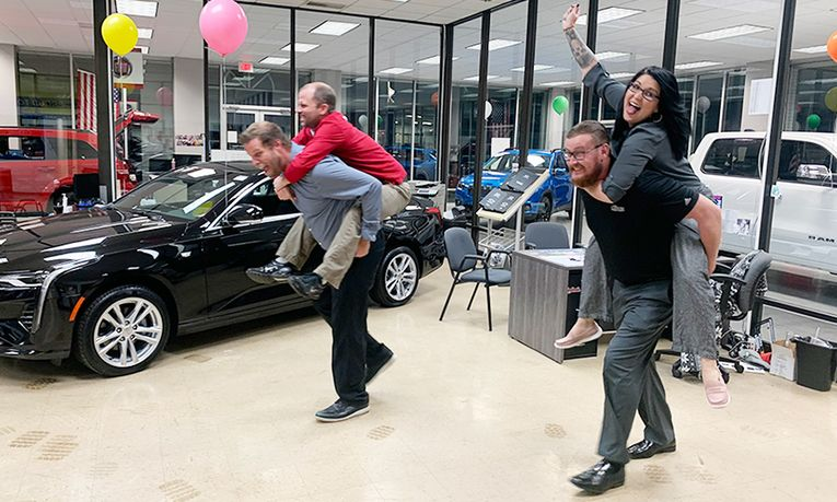 Business Manager Skyler McKinley and Special Finance Manger Robb Davis, riding piggyback, left, race Sales Professionals Dustin Teel and Danyalle Uremovich.? The losers bought lunch.