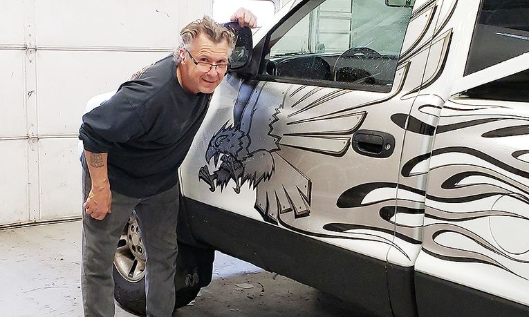 Collision Center Technician John Becka shows off his work on his last job before retiring.