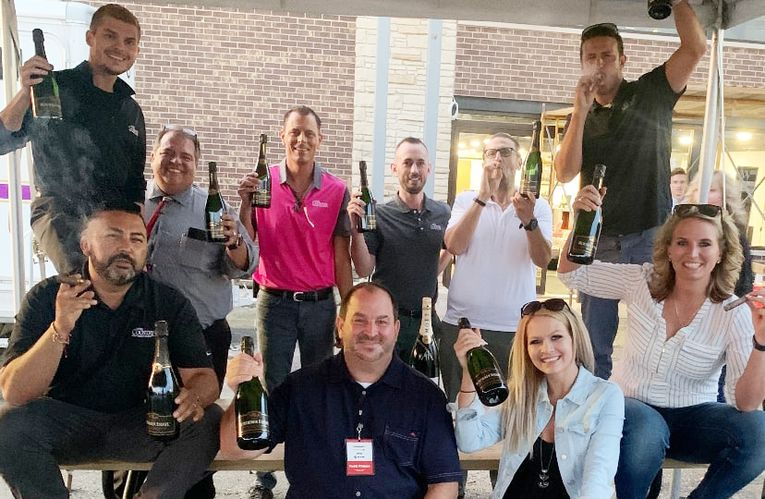 Staff members celebrate hitting an all-time sales record in July.