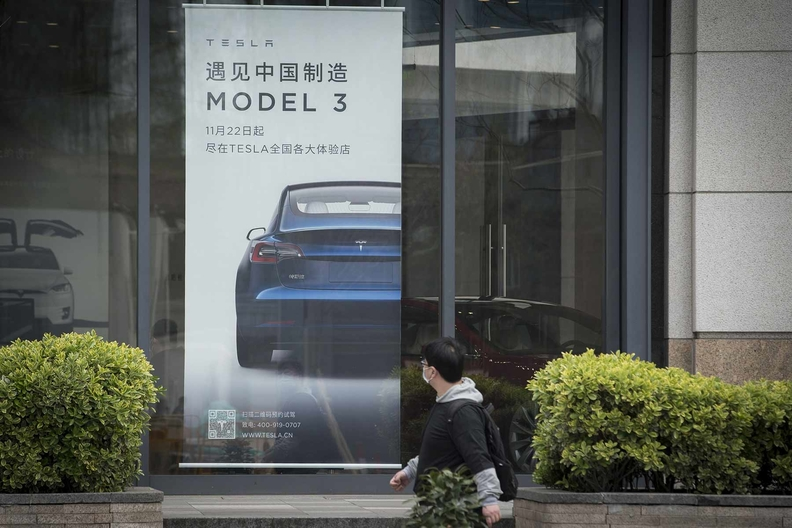 Man walks by a Tesla Model 3 sign in China