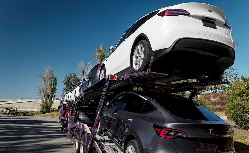 Tesla cars being transported for sale