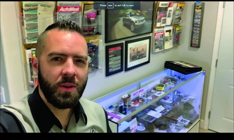 Tyson Hugie, in a screenshot from his video tour, shows memorabilia that is part of an Acura showroom in his house and garage.