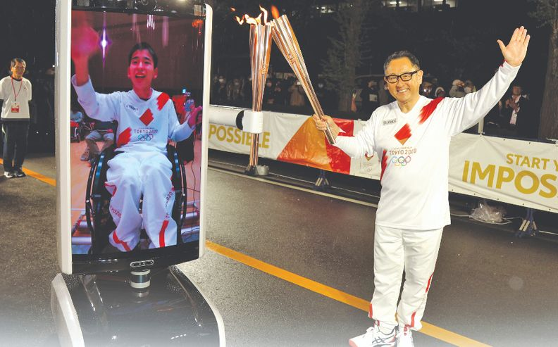 Toyota President Akio Toyoda, right, made an appearance during the Summer Olympics torch relay, which also marked the debut of the automaker's T-TR2 tele-presence robot.