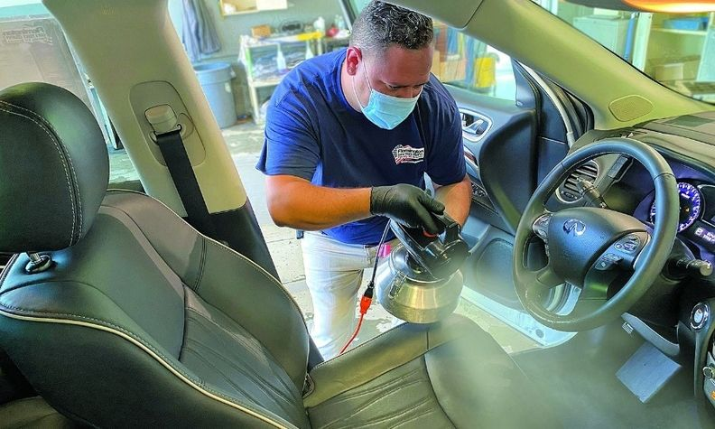 Jose Carbajal of Premier Detailing II applies antimicrobial product 360 Shield at Flemington Car & Truck Country.