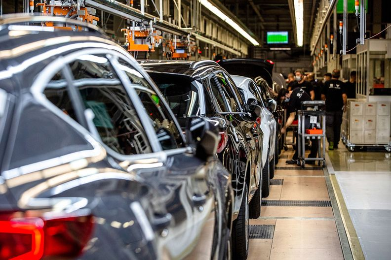Cars roll down an assembly line