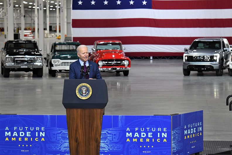 President Joe Biden speaks at Ford Motor Co.'s Rouge Electric Vehicle Center with un-camouflaged F-150 Lightning model (right) in the background.