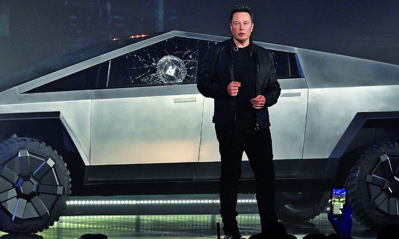 Elon Musk and Cybertruck with accidental hole, here; T-shirt with commemorative hole, below