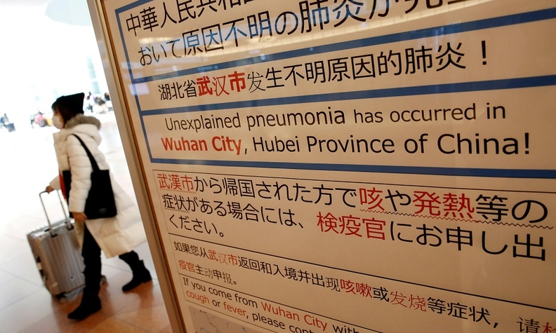 A woman wearing a mask walks past a quarantine notice about the outbreak of coronavirus in China at an arrival hall of Haneda airport in Tokyo.