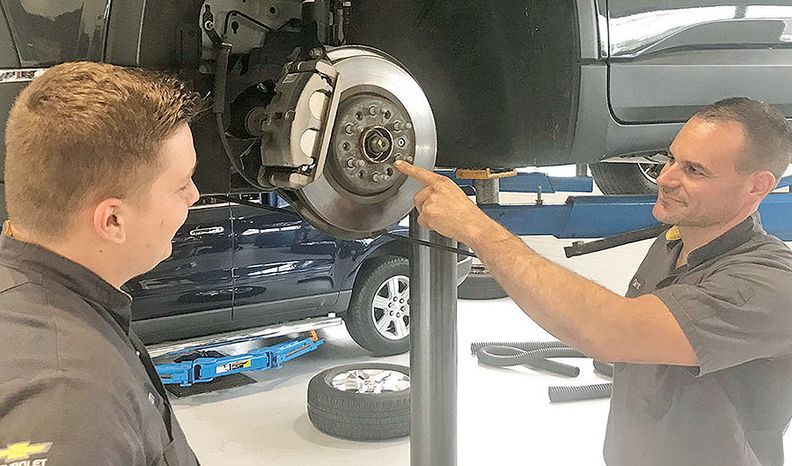 At Faulkner Chevrolet Lancaster, Master Technician Derrick Wenger, right, and trainee Keegan Martin button up a brake job. Martin has been paired with Wenger in Faulkner's mentor program.