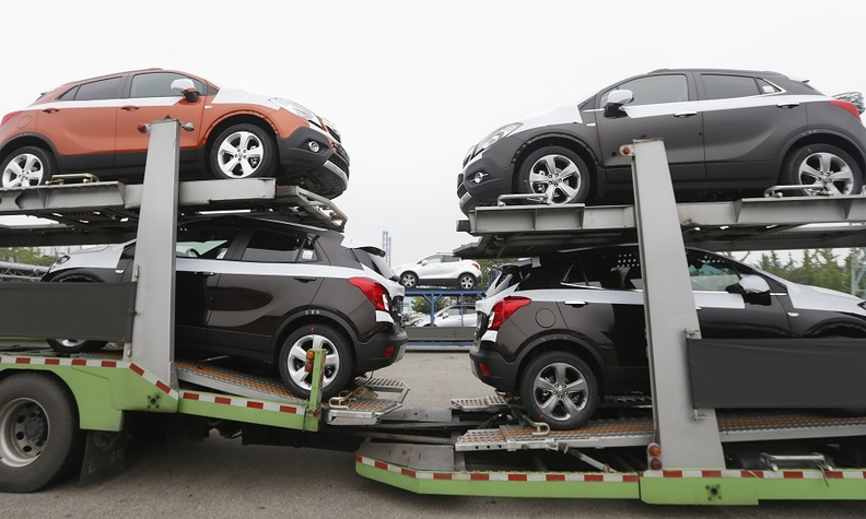 Cars made by GM Korea are seen on trucks.