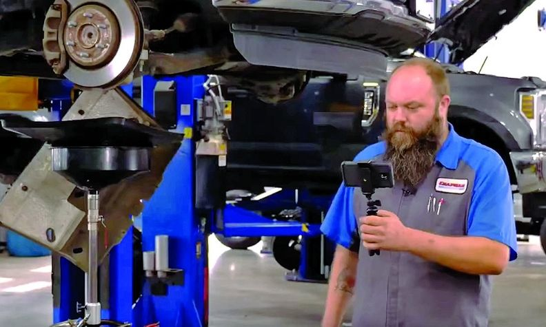 A tech uses a cellphone that features iService software to record video to send to a customer detailing repairs needed on the customer's vehicle.