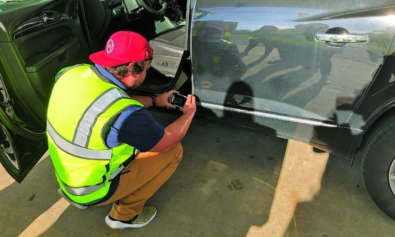 A vehicle inspector at a Manheim auction center demonstrates the process.