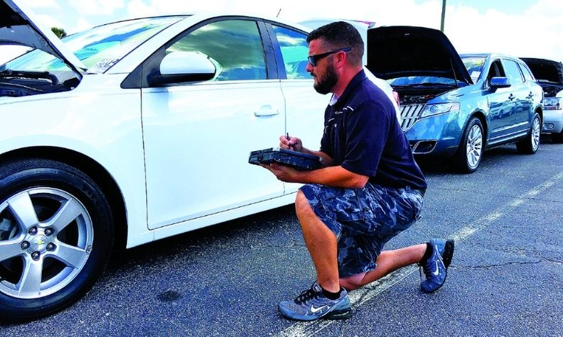 A Manheim inspector evaluates a vehicle after check-in.