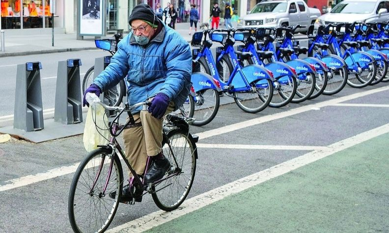 A man rides by the bicycles of New York sharing system Citi Bike. Demand for bikes is on the rise.
