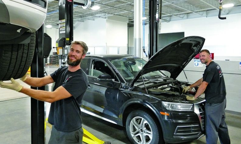 Adam Patterson, left, and Ian Farmer get two used vehicles ready for sale at Audi Nashua's used-car reconditioning center in New Hampshire. The center came online in January.