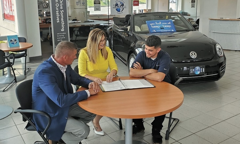 Spitzer Automotive's Tony Black, left, and Brittney Blowe with Igor Manasiev, a salesman at Spitzer Volkswagen Amherst, in Ohio. The group's sales program has expanded beyond its Mansfield stores.