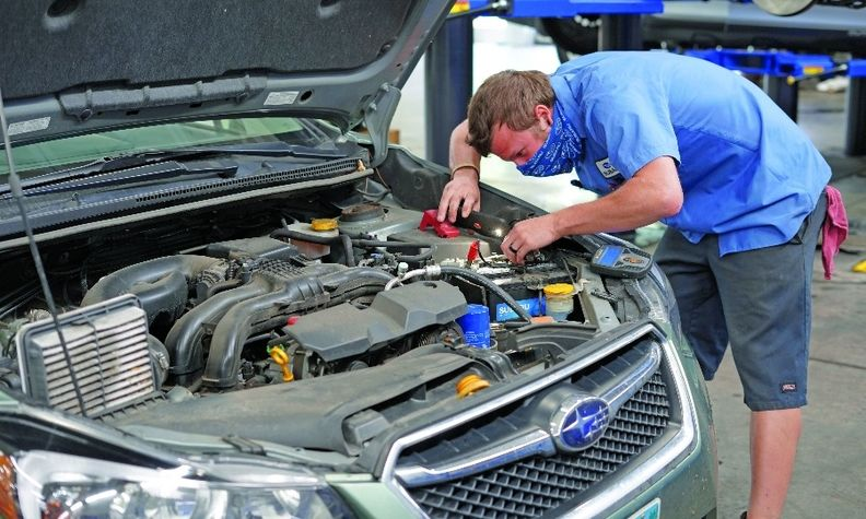 Justin Rossberg, a journeyman tech, works on a Subaru that was picked up for service.