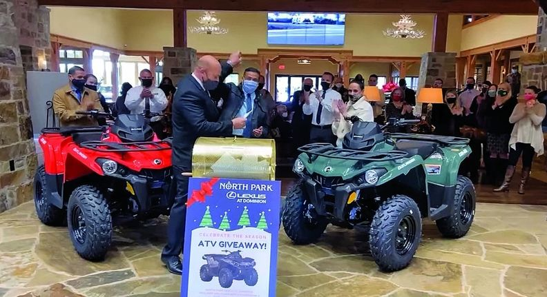 General Manager James Cole high fives sales consultant James Garza, who win an ATV in a drawing.
