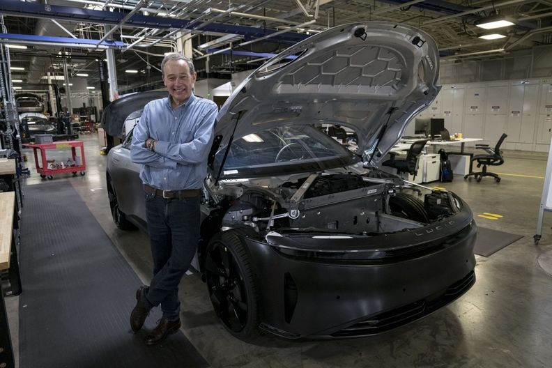 Lucid CEO Peter Rawlinson next to a Lucid Air